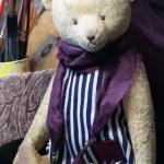 плюшевый мишка в платье с полосками.