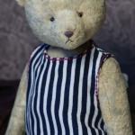 Медведь в полосатом платье и шёлковом шарфе.